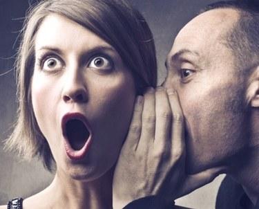 Man talking into woman's ear, woman looking surprised